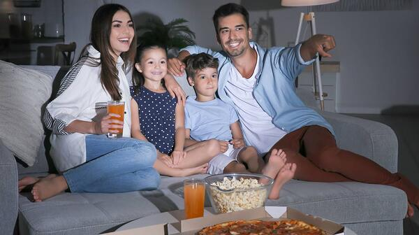 Happy-family-watching-TV-on-sofa-at-night-movie-night-SS-Featured
