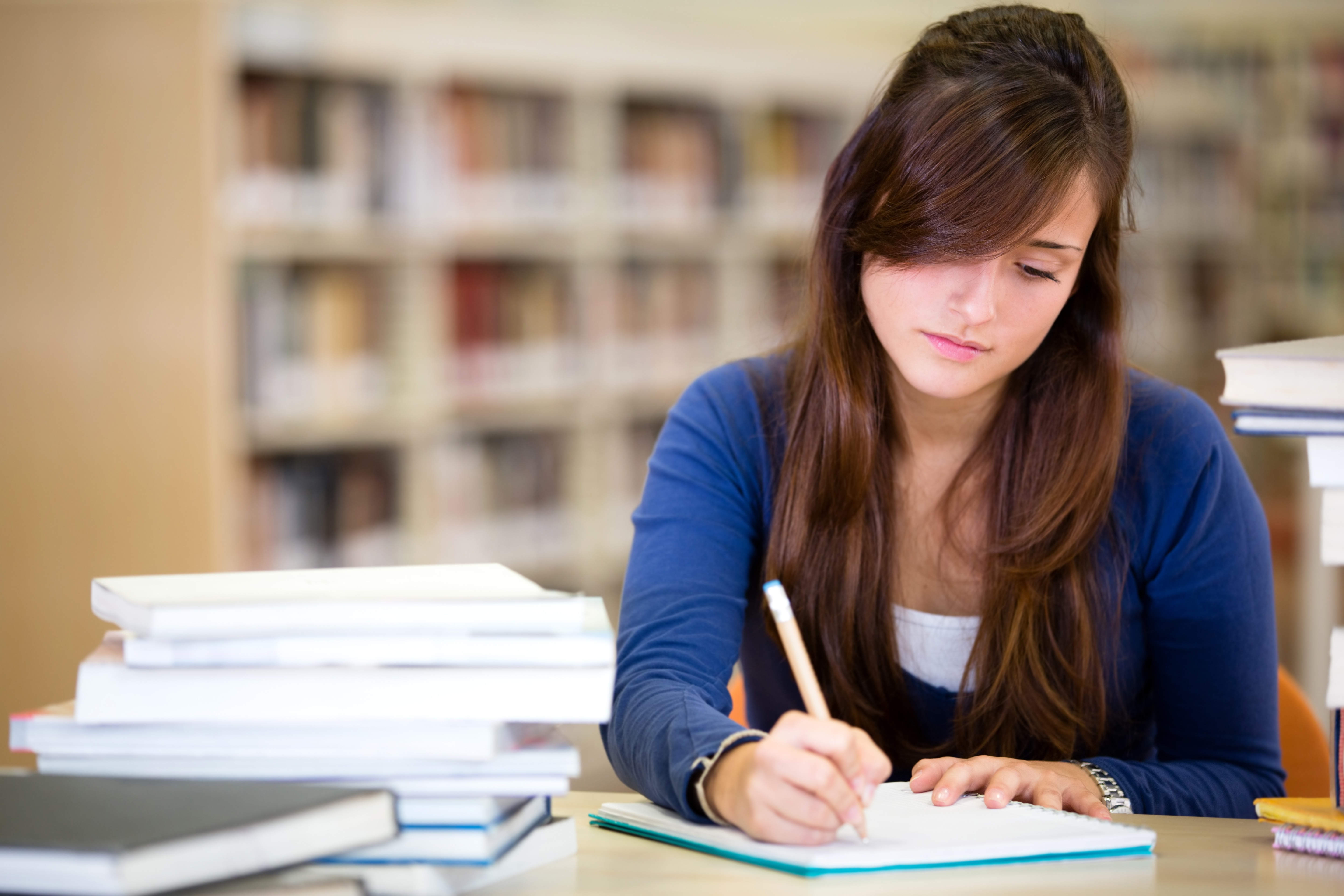 Woman studying at the library with books